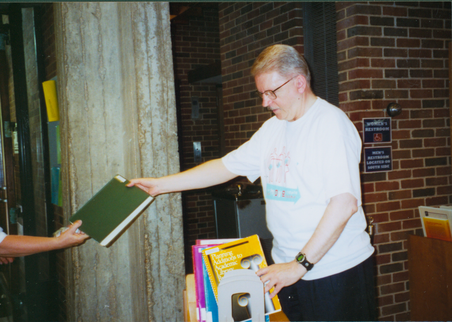 [Color photograph of Allen Mueller handing off a book for the book chain]