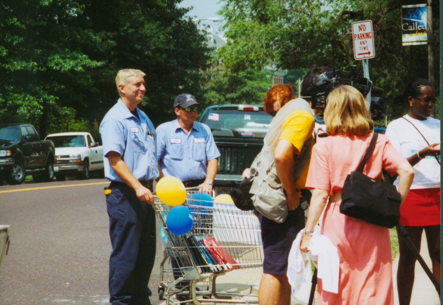 [Color photograph of facilities personnel with grocery carts]