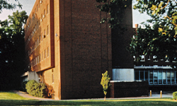 A color photo of Maria Hall, a five-story student dormitory made of yellow brick.