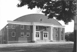 A black and white photo of the Nerinx Gymnasium, a two-story brick structure with a curved roof.