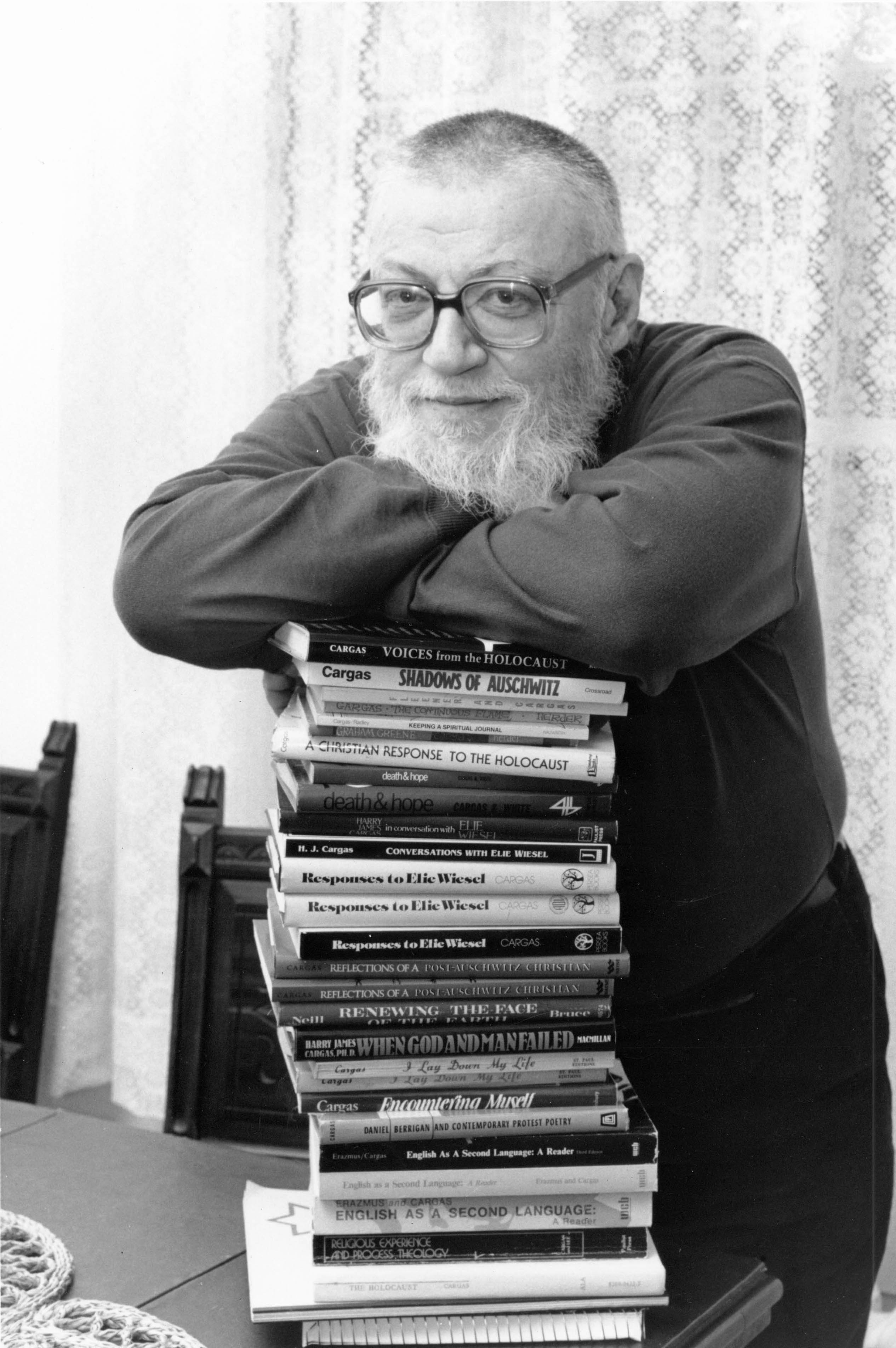 Black and white photograph of Dr. Cargas leaning on a stack of books
