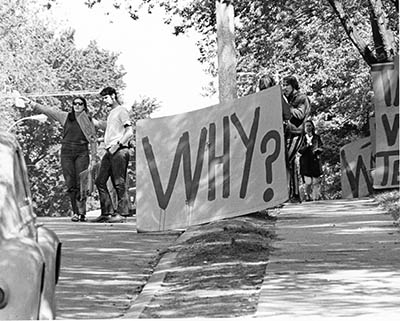 Black and white photograph of students with large sign reading WHY?