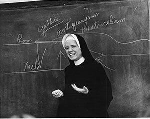 Black and white photograph of Marita Woodruff in habit at the blackboard